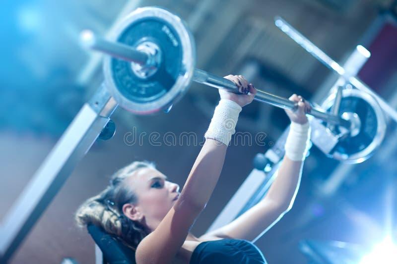 Entrenamiento del peso de la mujer joven foto de archivo