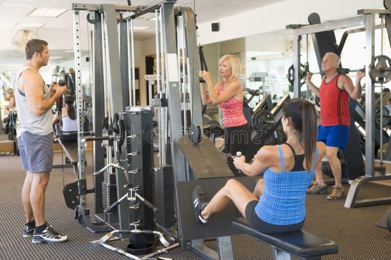 Entrenamiento del peso del grupo de personas en la gimnasia fotografía de archivo