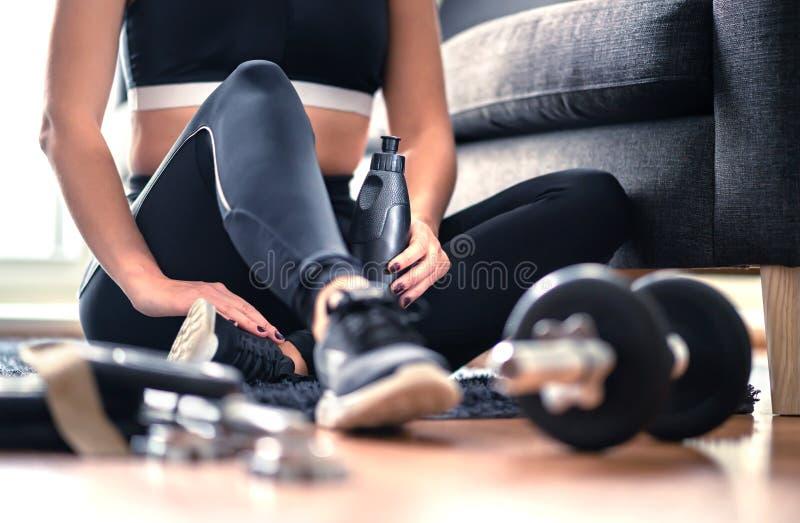 Entrenamiento, entrenamiento del peso y concepto caseros del ejercicio de la aptitud Mujer en la ropa de deportes que se sienta e foto de archivo libre de regalías