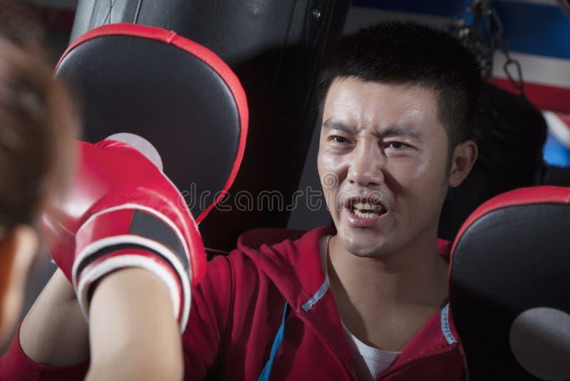 Entrenamiento del sofá del boxeo con el estudiante que sostiene los cojines del boxeo fotos de archivo