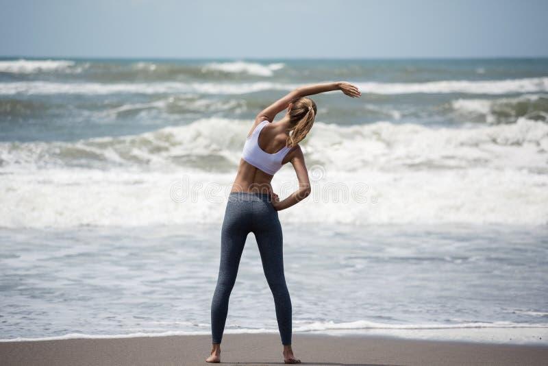 Entrenamiento delgado joven de la mujer en la playa fotos de archivo