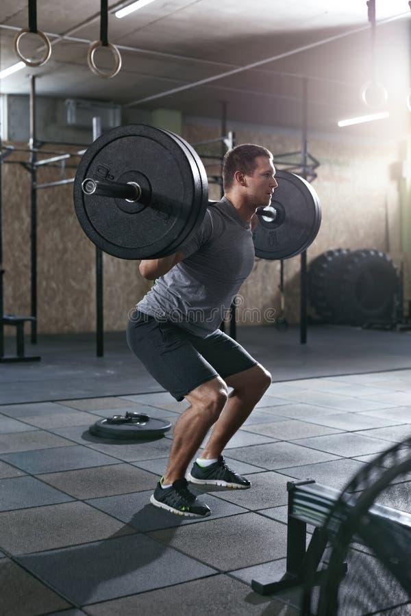 Entrenamiento en el gimnasio Los deportes sirven hacer posiciones en cuclillas con fila del Barbell foto de archivo