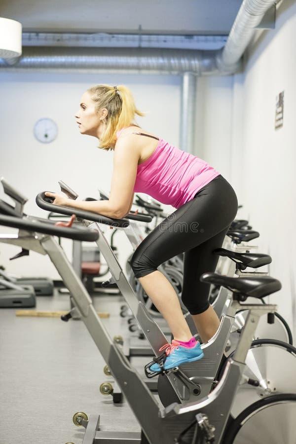 Entrenamiento escandinavo rubio caucásico de la muchacha de la aptitud en la bicicleta en el gimnasio imagenes de archivo
