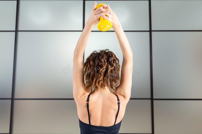 Entrenamiento femenino con dumbbell isolada imagen de archivo