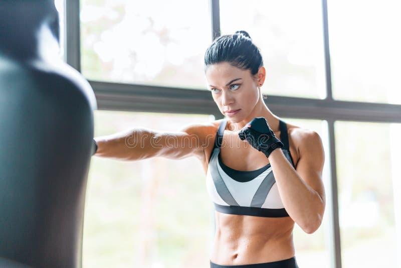 Entrenamiento femenino del boxeador con el saco de arena imágenes de archivo libres de regalías