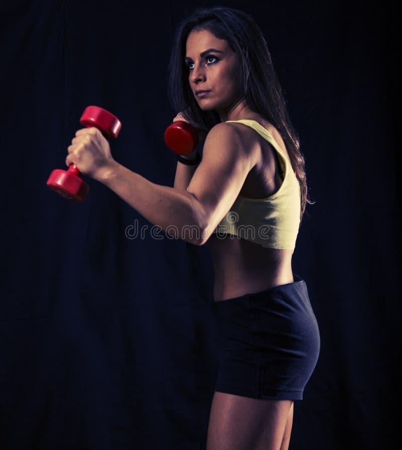 Entrenamiento fuerte de la mujer joven con pesas de gimnasia fotos de archivo