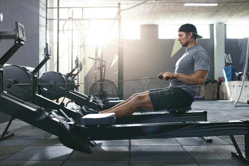 Entrenamiento funcional Hombre que hace ejercicio en remar la máquina en el gimnasio fotografía de archivo