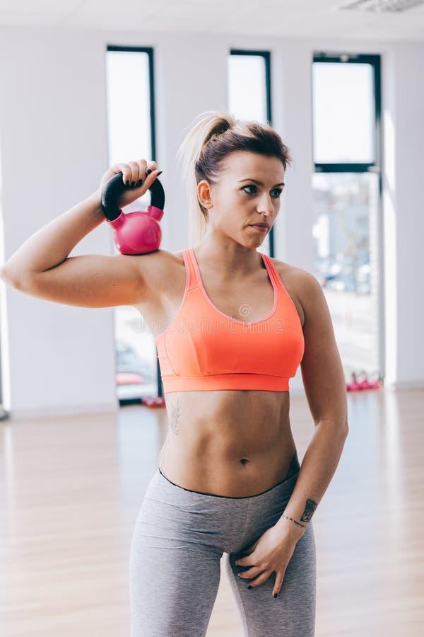 Entrenamiento joven del fitnesswoman con una caldera imagen de archivo libre de regalías