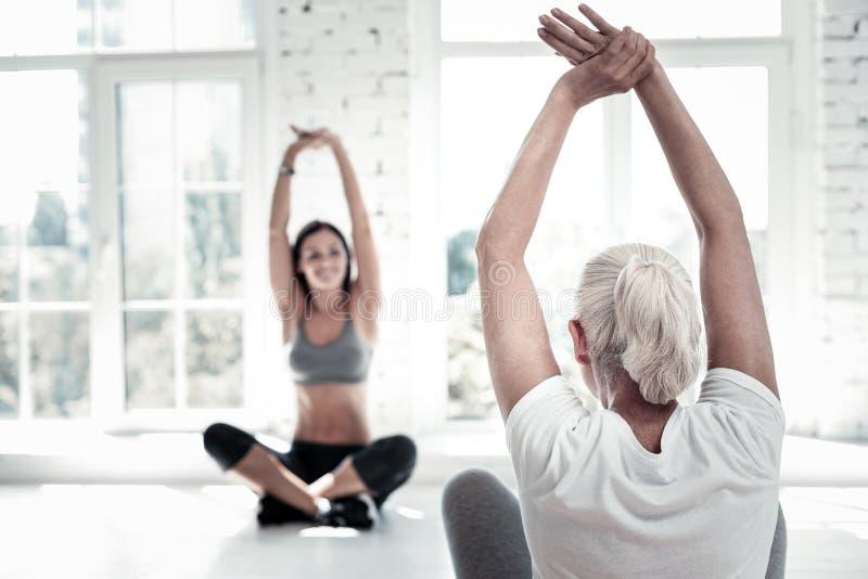 Entrenamiento jubilado de la señora y el estirar en el club de fitness foto de archivo