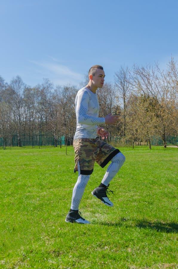 Entrenamiento masculino del verano de la ropa de deportes en el parque imagen de archivo