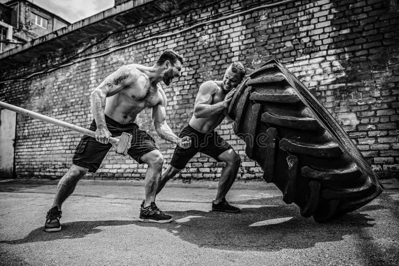 Entrenamiento muscular de dos atletas Neumático grande móvil del hombre descamisado muscular de la aptitud imagen de archivo libre de regalías
