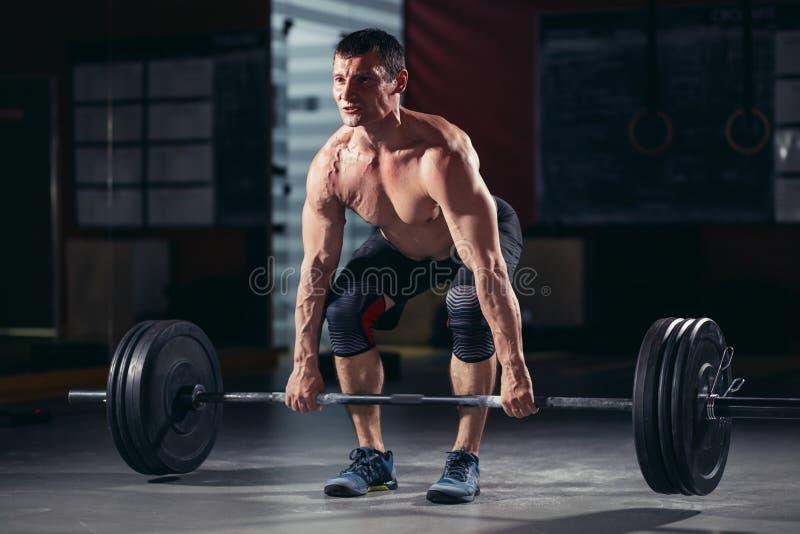 Entrenamiento muscular del hombre con el barbell en el gimnasio imagenes de archivo
