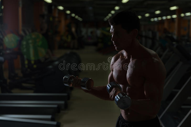 Entrenamiento muscular del hombre con pesas de gimnasia en sitio oscuro fotografía de archivo libre de regalías