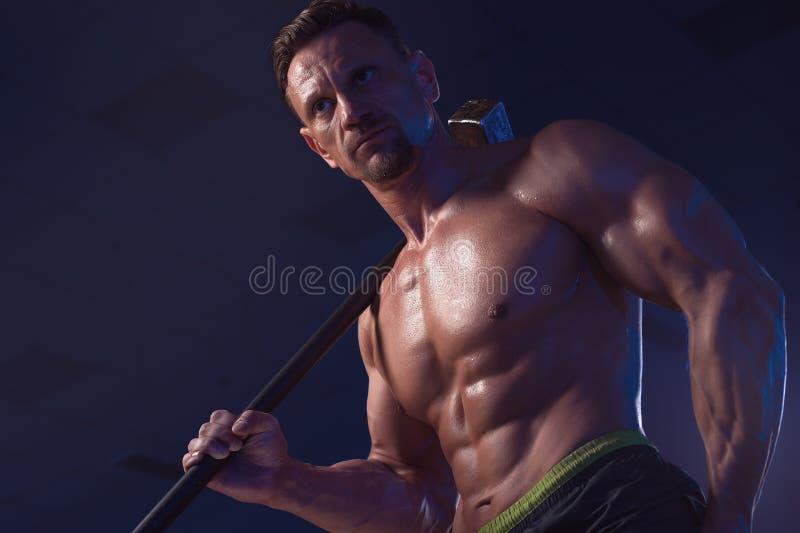 Entrenamiento muscular del hombre fuerte con el martillo imagen de archivo libre de regalías