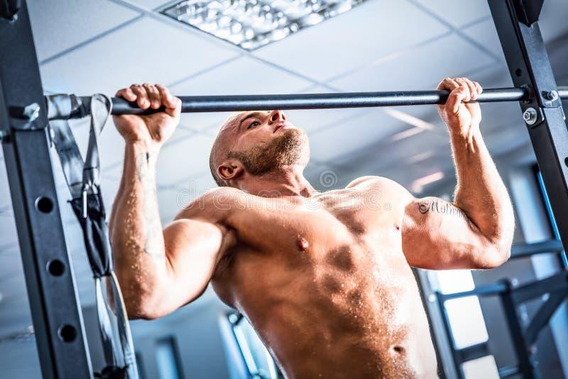 Entrenamiento muscular del hombre fuerte en un gimnasio imagen de archivo