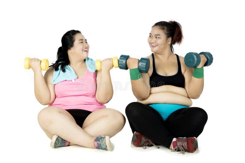 Entrenamiento obeso de la gente con pesas de gimnasia imagen de archivo libre de regalías