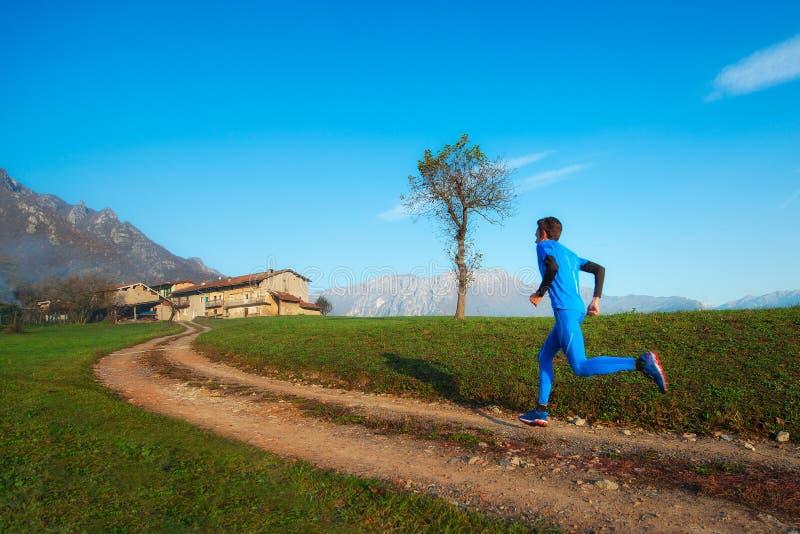 Entrenamiento profesional del atleta del corredor en una suciedad de la montaña imagenes de archivo