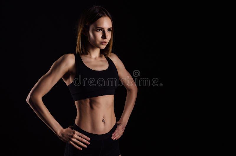 Entrenamiento que hace femenino muscular deportivo con las pesas de gimnasia aisladas en fondo negro La mujer joven atlética hace imagen de archivo