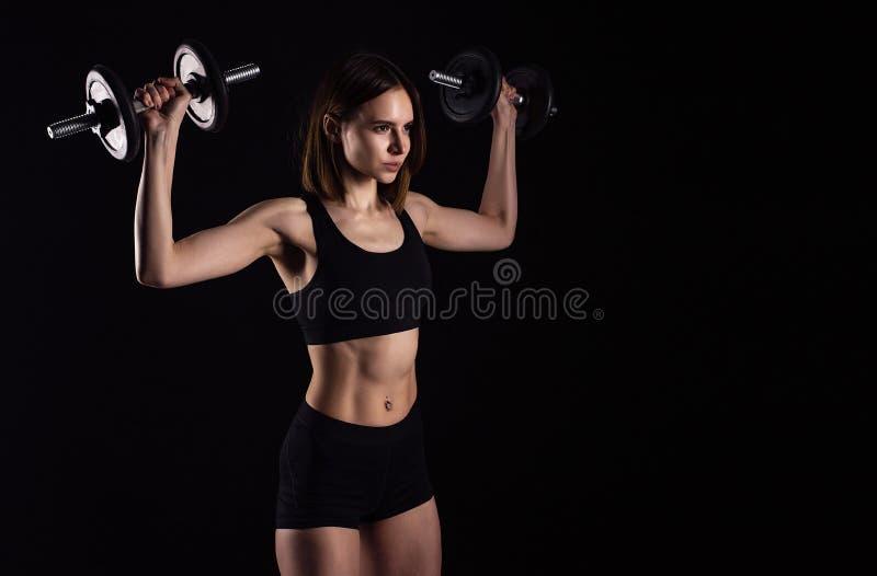 Entrenamiento que hace femenino muscular deportivo con las pesas de gimnasia aisladas en fondo negro La mujer joven atlética hace imagen de archivo libre de regalías