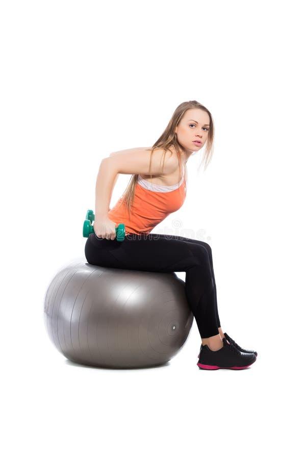 Entrenamiento rubio joven con pesas de gimnasia imagen de archivo libre de regalías