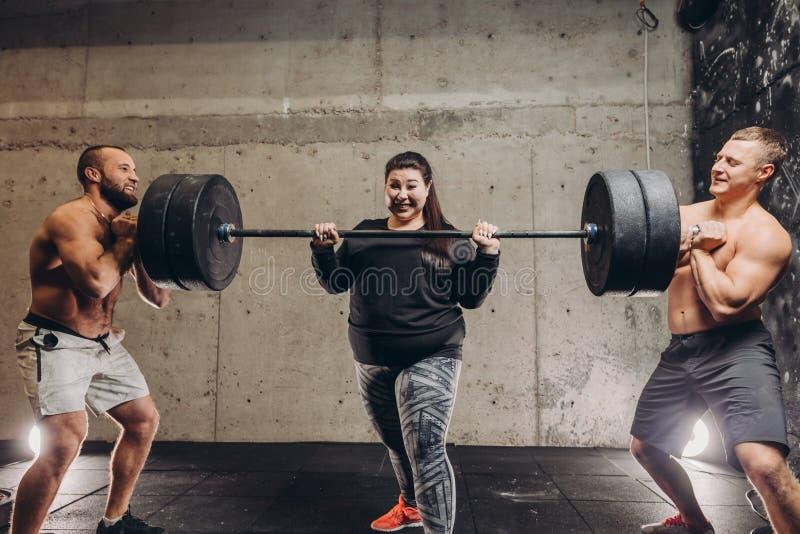 Entrenamiento sudoroso loco gordo de la mujer con los hombres en el gimnasio foto de archivo libre de regalías