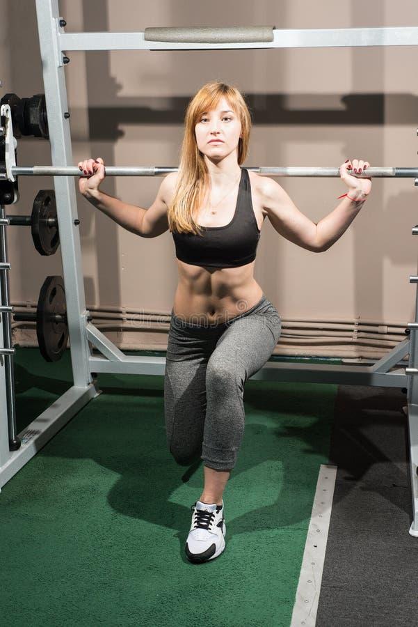 Entrenan al atleta en un gimnasio con un barbell fotografía de archivo libre de regalías