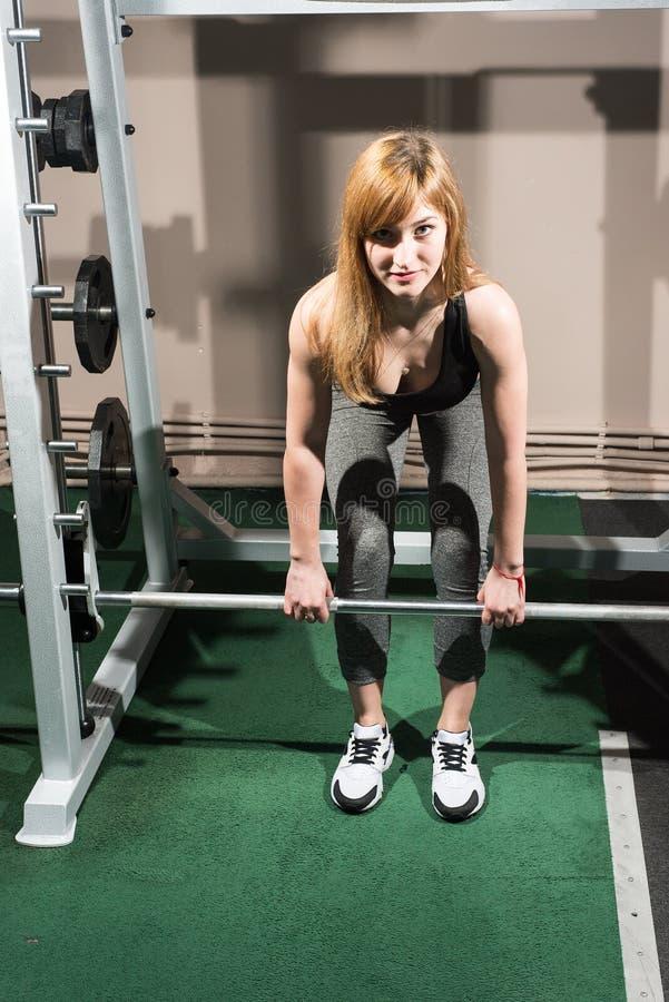 Entrenan al atleta en un gimnasio con un barbell fotos de archivo libres de regalías