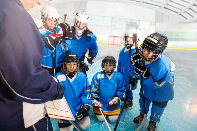 Entrene hablar con el equipo de hockey del ` s de los niños en pista imágenes de archivo libres de regalías