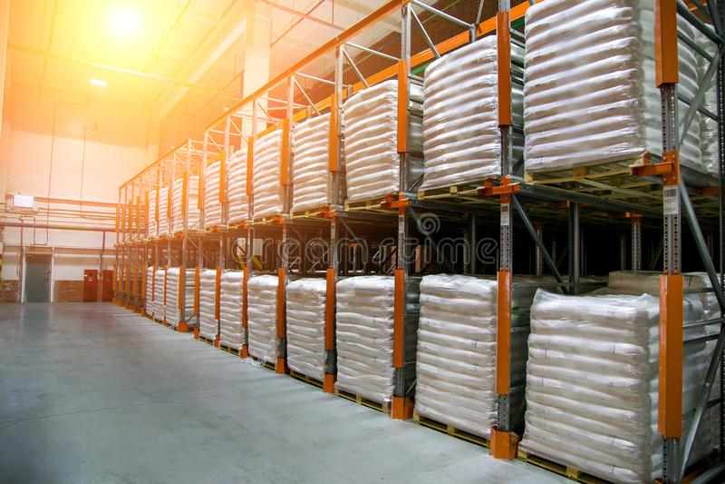 Entrepôt de hangar avec des rangées des étagères avec les sacs en polyéthylène blancs avec la production de finition d'usine photo stock