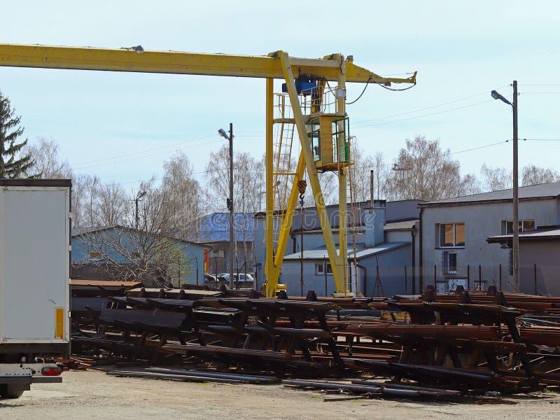 Entrepôt et distribution des produits métalliques sous le ciel ouvert Grue et voiture de rail de chargement dans l'entrepôt Branc photos stock