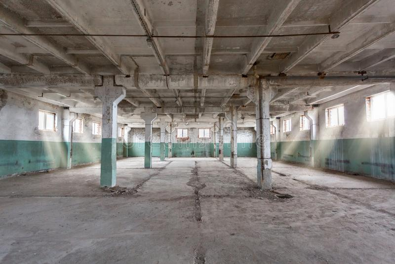 Entrepôt industriel avec des murs, des planchers, des fenêtres et des piliers de ciment avant la construction, transformant, réno photographie stock libre de droits