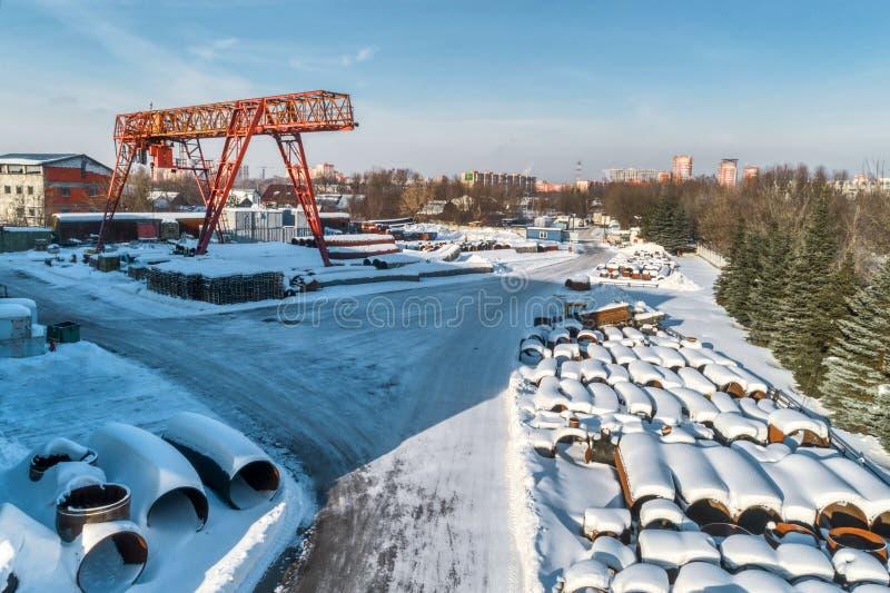 Entrepôt ouvert pour le stockage des tuyaux en métal de grand diamètre Une grue de portique est installée dans le territoire Jour photographie stock libre de droits