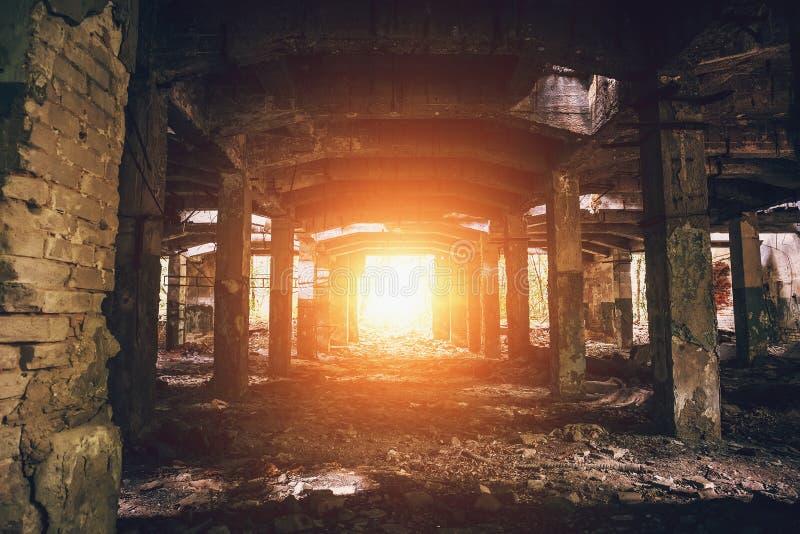 Entrepôt abandonné avec des colonnes, perspective foncée de tunnel avec la lumière lumineuse à la fin images stock