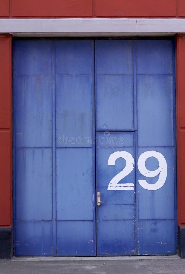 Entrepôt industriel extérieur avec la porte et la porte bleues âgées images libres de droits