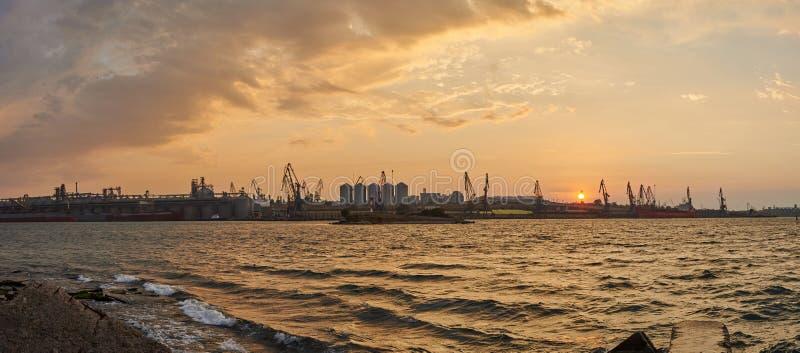 Entrepôts de cargaison dans le port maritime dans le lever de soleil photographie stock