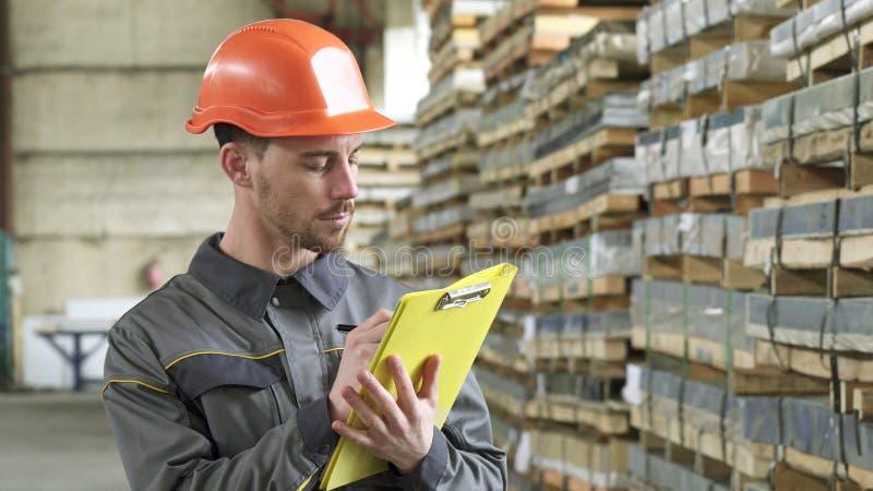 Entreposez l'écriture de travailleur sur son presse-papiers se tenant au stockage images stock
