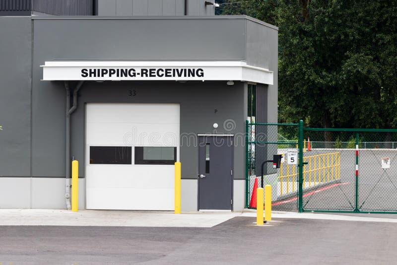 Entreposez l'expédition de bâtiment recevant la porte de garage et la déclenchez avec l'allée de route photographie stock