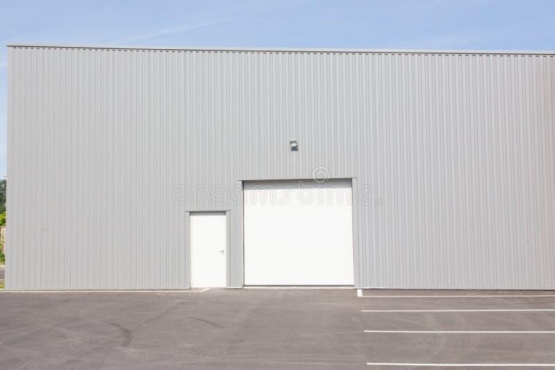 Entreposez le bâtiment avec le ciel bleu et la porte blanche images libres de droits