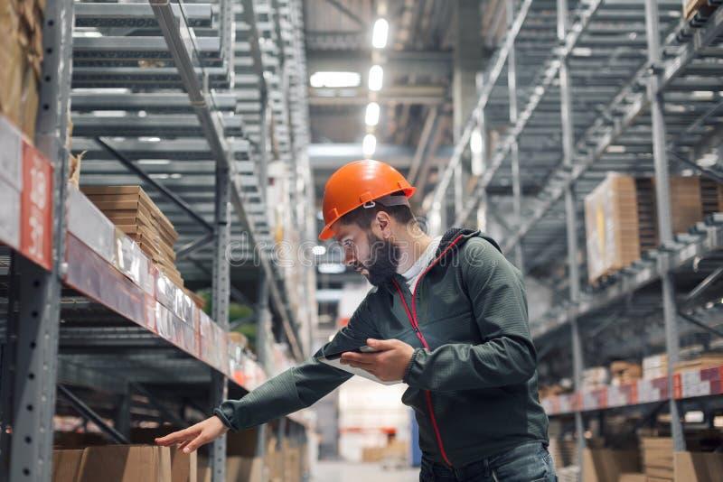 Entreposez le directeur vérifiant son inventaire dans un grand entrepôt images stock