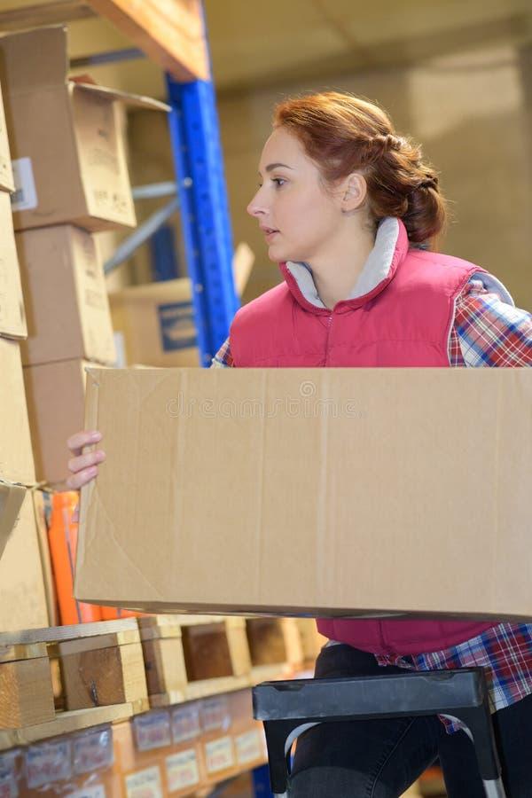 Entreposez le travailleur prenant le paquet dans l'étagère dans l'entrepôt photo stock