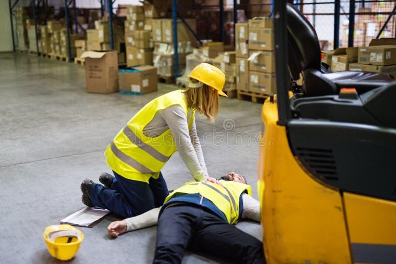 Entreposez les travailleurs après un accident dans un entrepôt images libres de droits