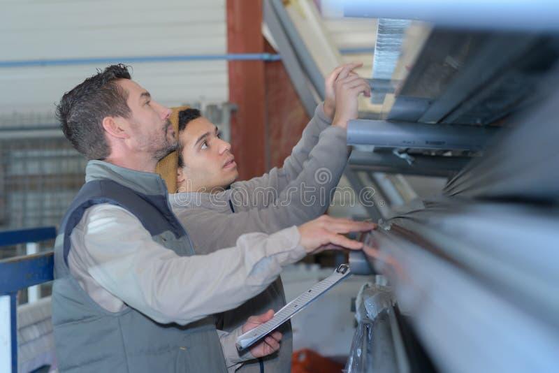 Entreposez les travailleurs atteignant pour quelque chose dans des marchandises de stockage en rayons image libre de droits