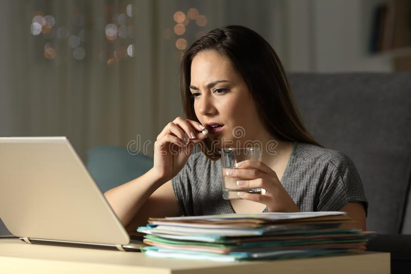 Entreprenör som arbetar sena timmar som tar smärtstillande medelpreventivpilleren royaltyfri fotografi