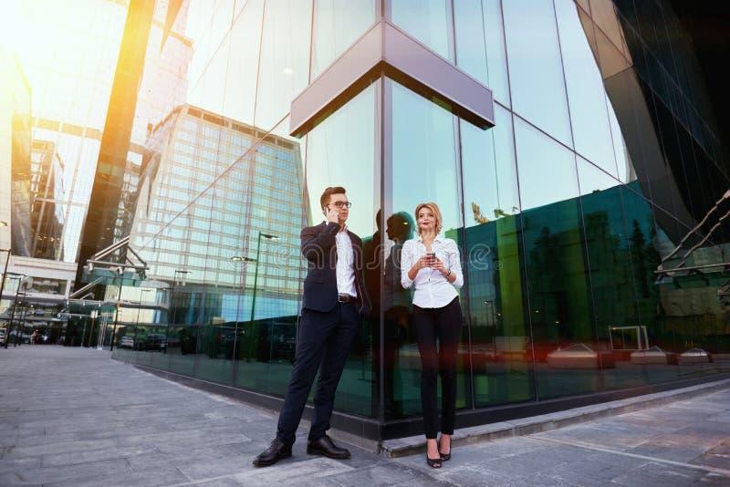 Entreprenör två använder deras celltelefoner, medan väntar partnern utomhus arkivfoton