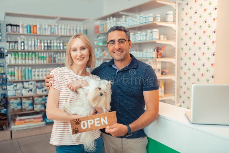 Entreprenörer som rymmer den vita hunden, når de har öppnat eget husdjur, shoppar arkivfoto