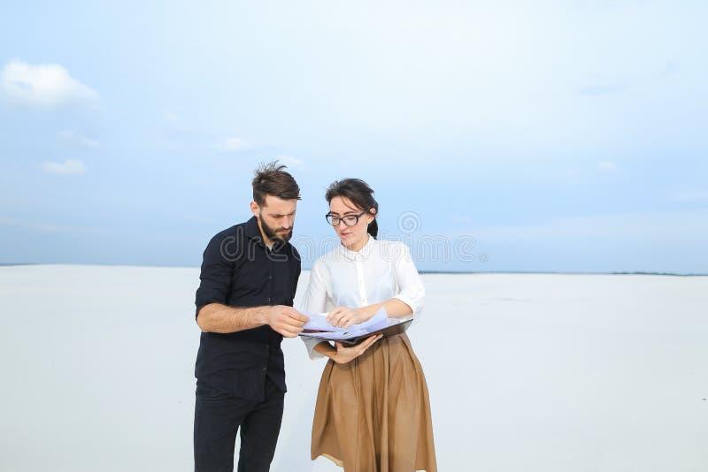 entreprenörman och kvinnligt diskuterande projekt av stranden ar arkivfoton