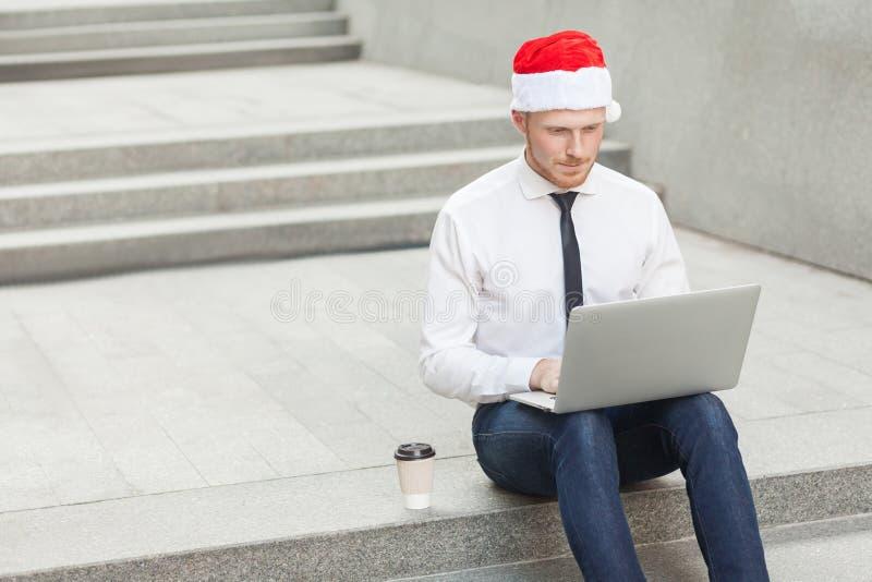 entreprenadisering Ljust rödbrun man, i att arbeta för santa hatt som är utomhus- arkivfoton