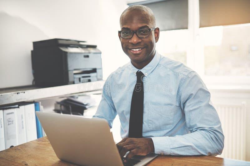 Entrepreneur africain de sourire travaillant dans un siège social photo stock