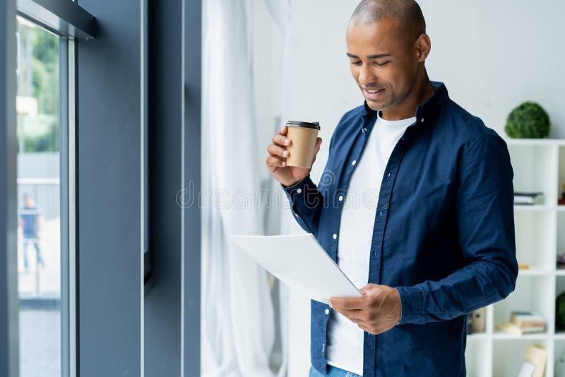 Entrepreneur africain réussi étudiant des documents avec le regard attentif et concentré, café potable au café foncé photos libres de droits