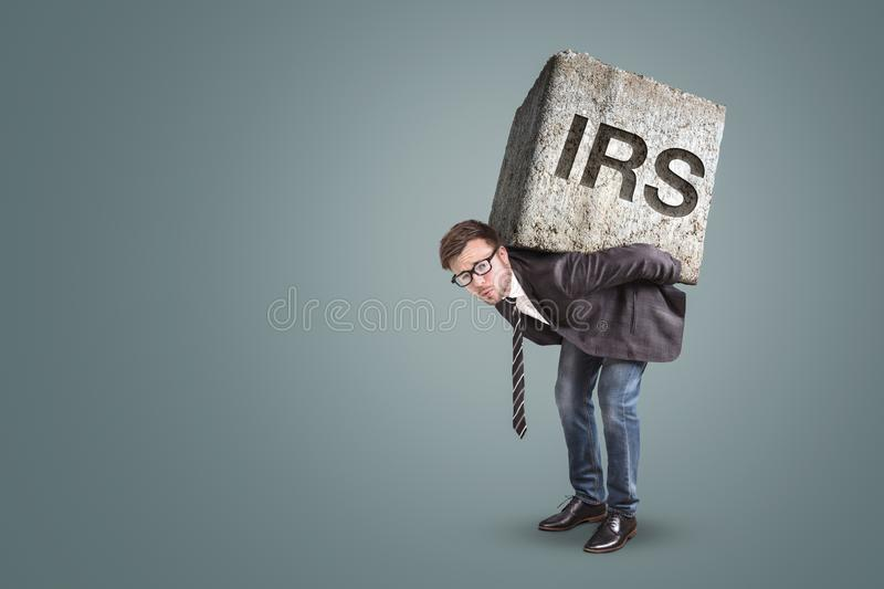 Entrepreneur carrying a large stone with engraved IRS letters. Businessman bending under a heavy stone with the letters IRS on it - tax office concept royalty free stock photography